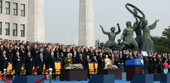 President Park Geun-hye, former President Lee Myung-bak, and other participants of the inauguration salute the national flag at the presidential inauguration ceremony held at the National Assembly in Seoul on February 25 (National Assembly = Jeon Han).