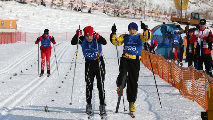 The athletes cross the finish line during the cross country running event on January 30, the first day of the Special Olympics (photo: Jeon Han).