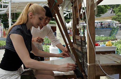 A foreign tourist participates in a hands-on ramie fabric-weaving activity offered at the Hansan Mosi Cultural Festival