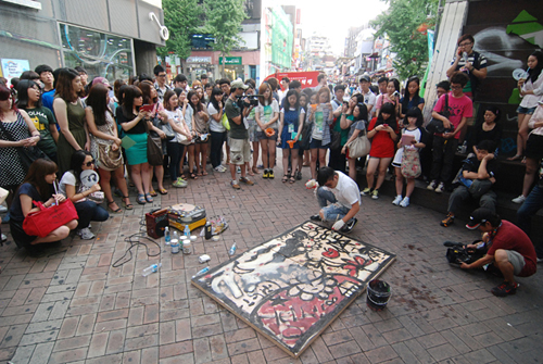 Artist Shin Juwook works on his craft before a public audience at one of the Fringe's many street events (photo courtesy of Seoul Fringe Festival).