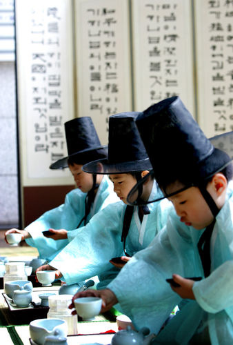 Young boys reenact a traditional Korean tea ceremony. As a cultural practice, tea ceremonies higlighted expressions of propriety as upheld in Confucian and as well as Buddhist traditions (photo: Yonhap News).